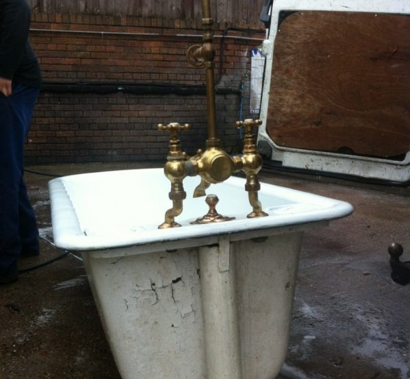 Antique and salvaged bath with original shower head and curtain rail